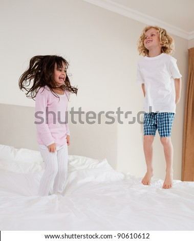 Portrait of children jumping on a bed - stock photo