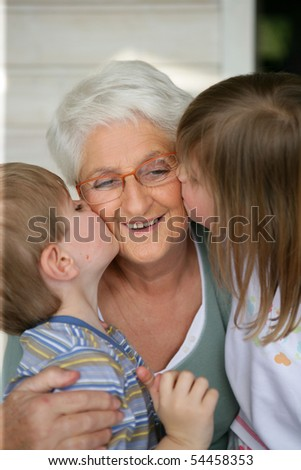 Portrait of children kissing a senior woman on the cheek - stock photo