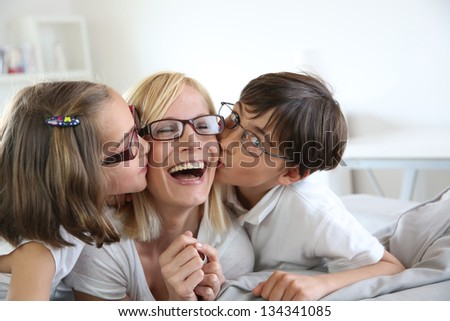 Portrait of children kissing her mom - stock photo