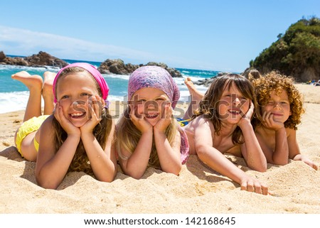 Portrait of children laying on sand at beach. - stock photo