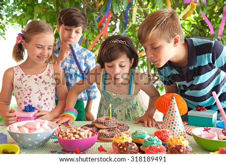 Portrait of children together joyfully smiling, blowing candles in a colorful birthday party in a home garden with decorations, home outdoors. Kids fun active lifestyle and expressions, exterior. - stock photo