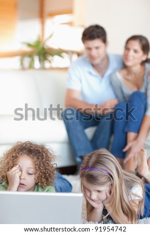 Portrait of children using a laptop while their parents are watching in their living room - stock photo