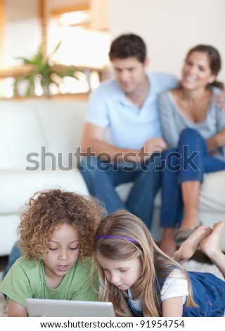 Portrait of children using a tablet computer while their parents are watching in their living room - stock photo