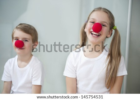 Portrait of children wearing clown noses - stock photo