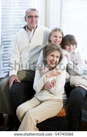 Portrait of children with grandparents together at home - stock photo