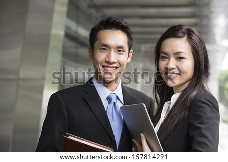 Portrait of Chinese business man and woman in a modern urban setting.  - stock photo