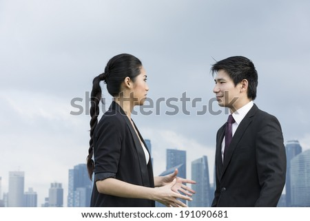 Portrait of Chinese business people talking outside. Urban Cityscape in the background.  - stock photo