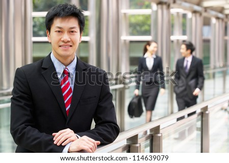 Portrait Of Chinese Businessman Outside Office With Colleagues In Background - stock photo