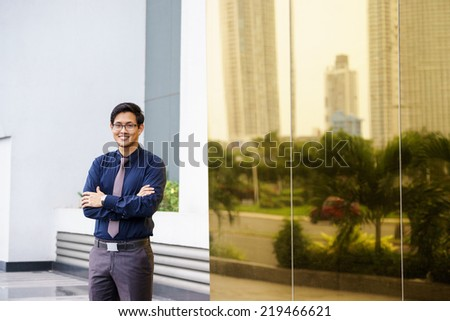 Portrait of chinese businessman standing with arms crossed near office building in Panama. Reflections of city on mirror - stock photo
