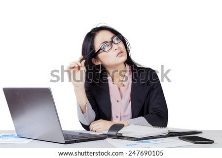 Portrait of chinese entrepreneur in business suit doing her job while thinking an idea - stock photo