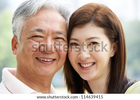 Portrait Of Chinese Father With Adult Daughter In Park