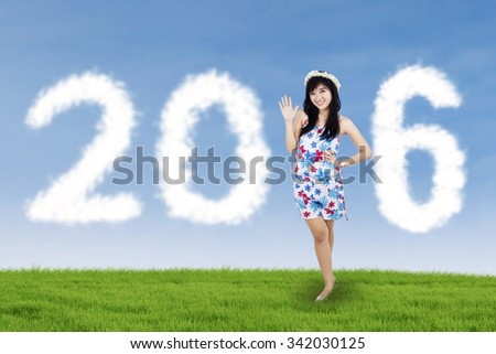 Portrait of chinese girl standing on the meadow with clouds forming numbers 2016