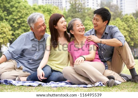 Portrait Of Chinese Parents With Adult Children Relaxing In Park Together