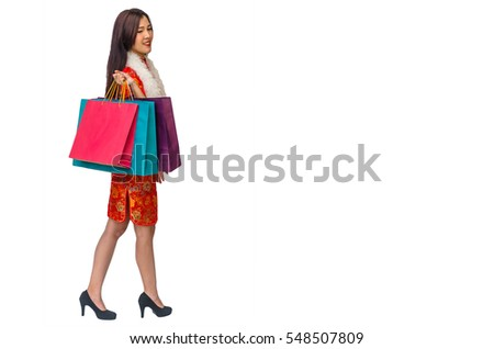 Portrait of Chinese woman wearing traditional Cheongsam clothes and holding shopping bags and expend dollars money for shopping in Chinese New Year festival isolated on white background.