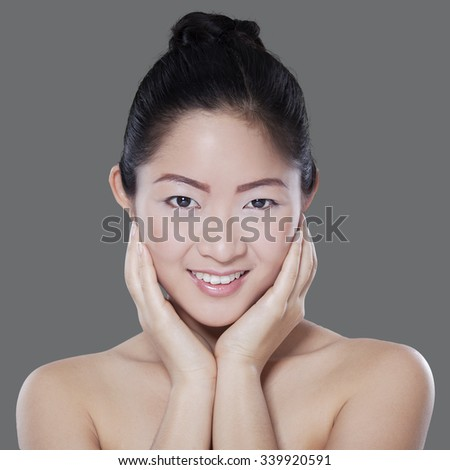 Portrait of chinese woman with beautiful face smiling at the camera in front of grey background - stock photo