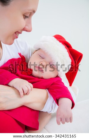 Portrait of Christmas baby is sleeping on mothers hands - stock photo