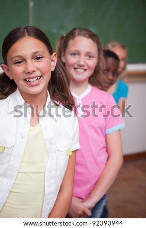 Portrait of classmates posing in a row in a classroom - stock photo
