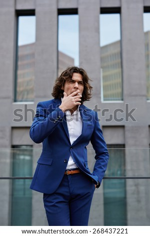 Portrait of classy gentleman smoking a cigar standing outdoors, handsome executive smoking cigarette during his work break - stock photo
