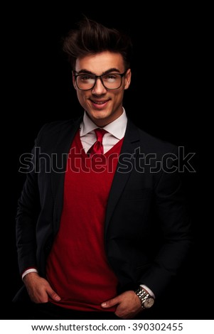 portrait of classy model in black suit wearing glasses posing with hands in pockets while looking at the camera in dark studio background