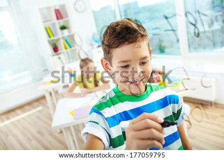 Portrait of clever boy doing sums on transparent board with schoolmate on background - stock photo
