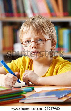 Portrait of clever boy drawing with highlighters - stock photo