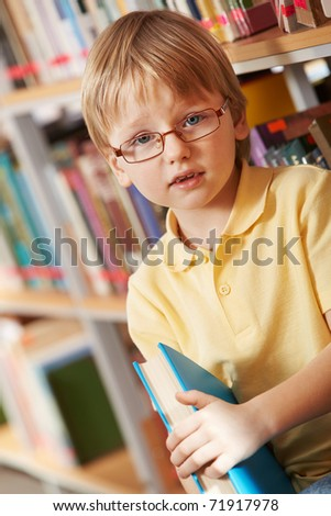 Portrait of clever boy holding book and looking at camera in library - stock photo