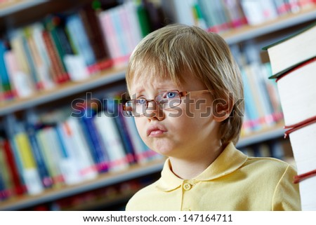 Portrait of clever boy in library - stock photo