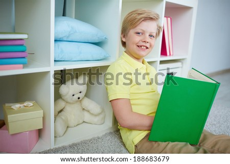Portrait of clever boy reading book at home - stock photo