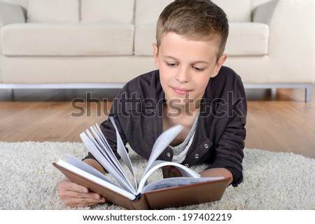 Portrait of clever boy reading book while lying on the floor at home - stock photo