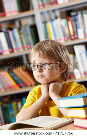 Portrait of clever boy thinking while reading book in library - stock photo