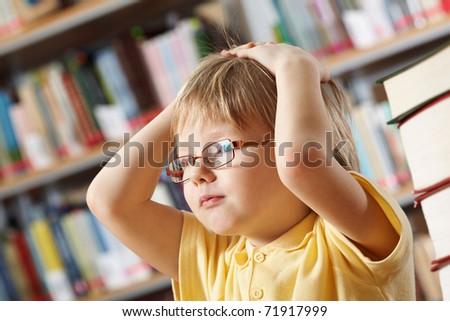 Portrait of clever boy touching his head - stock photo