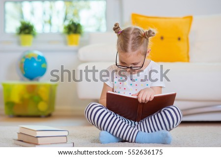 Portrait of clever little girl sitting with book on the floor with globe on the background