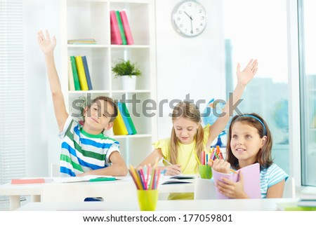 Portrait of clever schoolkids raising hands at workplace with their classmate near by - stock photo