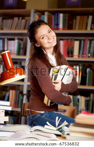 Portrait of clever student or young teacher with books looking at camera and smiling in college library