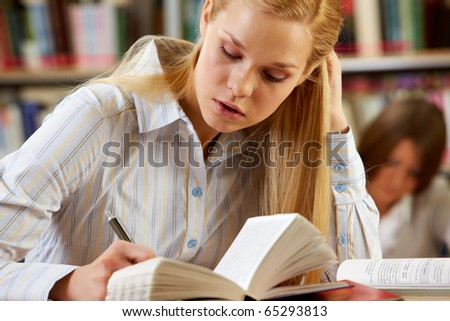 Portrait of clever student reading book in college library - stock photo