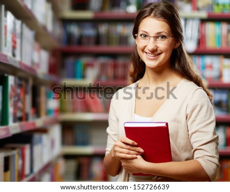 Portrait of clever student with book in college library - stock photo