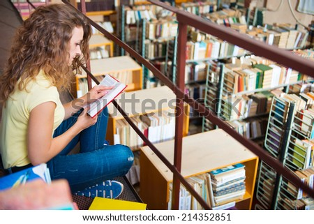 Portrait of clever student with books in college library  - stock photo
