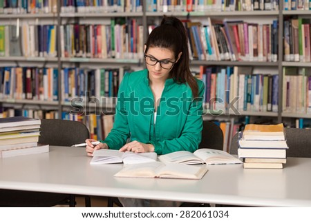 Portrait Of Clever Student With Open Book Reading It In College Library    Shallow Depth Of