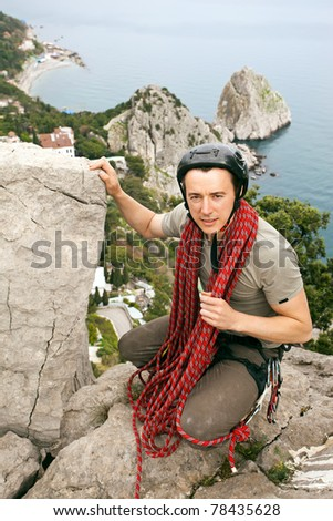 Portrait of climber on top of mountain against rocky coastline