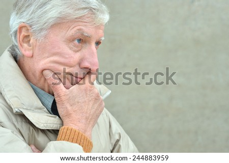 Portrait of cold senior man on grey background