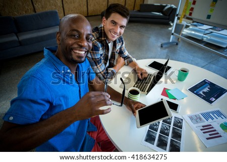 Portrait of colleagues at their desk in the office - stock photo
