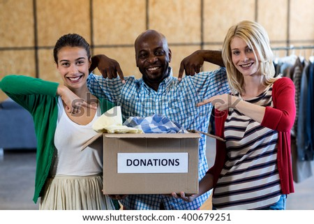Portrait of colleagues holding and pointing at donation box - stock photo