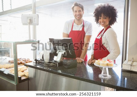 Portrait of colleagues posing behind the counter at the bakery - stock photo