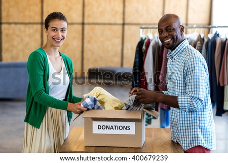 Portrait of colleagues sorting clothes from donation box in the office - stock photo
