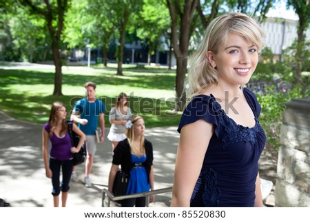 Portrait of college girl going college with friends in background - stock photo