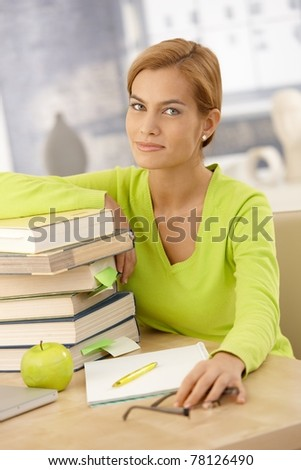 Portrait of college girl sitting at desk with books and notes, smiling at camera.?