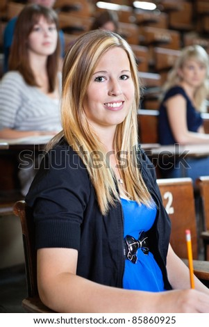 Portrait of college girl sitting in auditorium while classmates sitting in background - stock photo