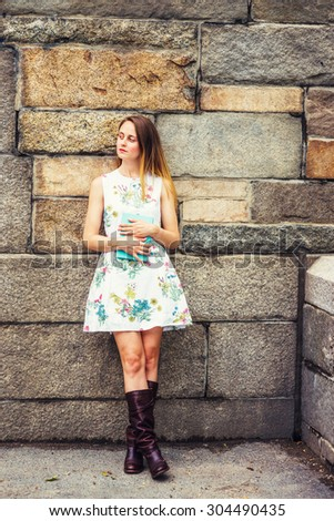 Portrait of College Student. A girl wearing flower patterned, sleeveless, white dress, brown leather high riding boots, holding green book, crossing legs, standing by rocky wall. Instagram effect - stock photo