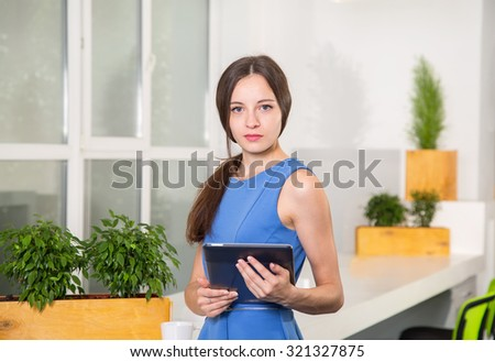Portrait of college student in classroom. Girl student holding a digital tablet. Young student using a tablet computer in a room.  - stock photo