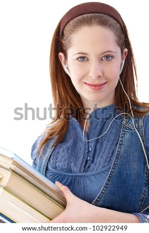 Portrait of college student listening music, holding books in hands, smiling. - stock photo
